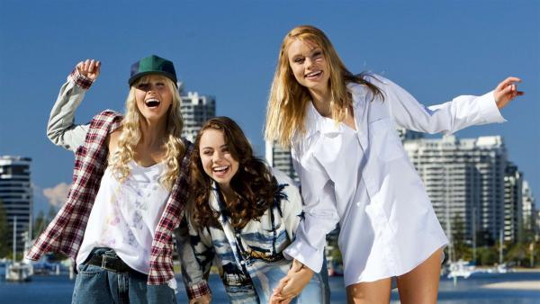 V.l.n.r.: Sirena (Amy Ruffle), Nixie (Ivy Latimer) und Lyla (Lucy Fry) vor der Skyline der australischen Goldcoast. | Rechte: ZDF/Jonathan M. Shiff Prod./Vince Valitutti