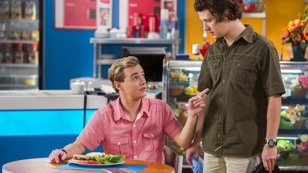 Cam (Dominic Deutscher, li.) versucht David (Rowan Hills, re.) von seiner neuen Hamburger-Kreation zu überzeugen.   Rechte: ZDF/Jonathan M. Shiff Prod./Vince Valitutti