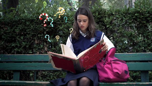 Mia (Rosabell Laurenti Sellers) ist nicht gerade begeistert von ihrem neuen Internat. Da kommt das Geschenk ihrer Eltern genau richtig - ihr längst vergessenes Lieblingskinderbuch und ein merkwürdiger Armreif. | Rechte: ZDF/Carlo Valentini