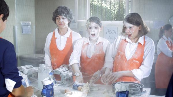 Mia (Rosabell Laurenti Sellers, Mi.), Paula (Saphia Stoney, re.) und Vincent (Adrian Moore, li.) haben viel Spaß beim Kochunterricht. Doch gerade jetzt ruft das Orakel Mia nach Centopia.   Rechte: ZDF/Carlo Valentini