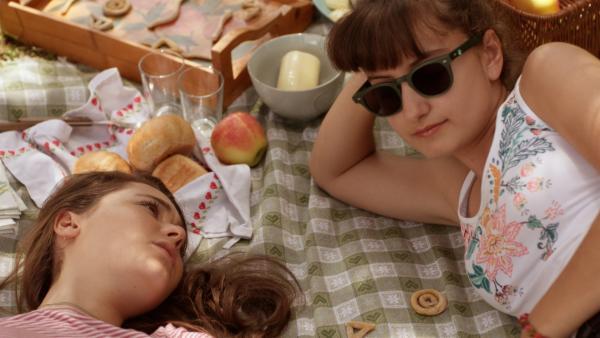 Mia (Margot Nuccetelli, l.) und Sara (Lucia Luna, r.) genießen die Sonne bei einem Picknick und reden über die Schule. | Rechte: ZDF/2017 Hahn & m4e Productions