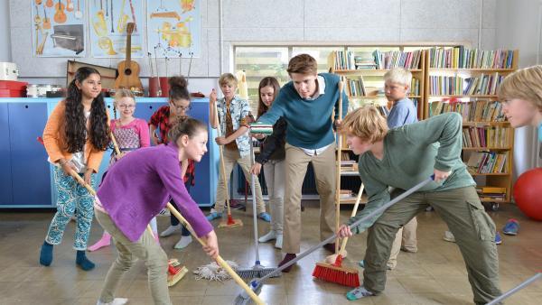 Herr Kees (Leendert de Ridder, m.) hat die Eishockey-Regeln mit seinen Schülern im Unterricht durchgenommen. Jetzt üben sie den praktischen Einsatz bei einem Match im Klassenzimmer.   Rechte: ZDF/Jaap Vrenegoor
