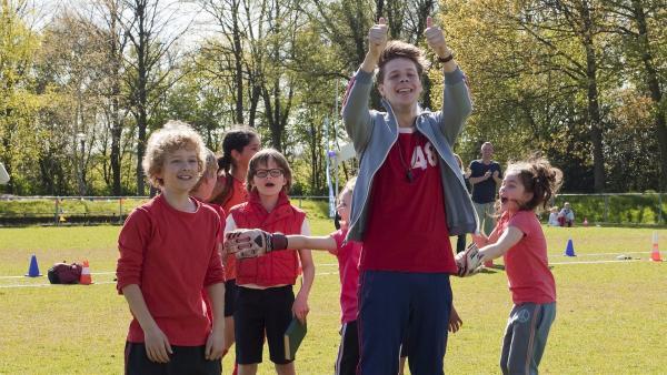 Herr Kees (Leendert de Ridder, r.v.) hält triumphierend die Daumen in die Höhe. Er hat als Trainer mit dem Fußballteam seiner Klasse 6b gewonnen. | Rechte: ZDF / Victor Arnolds