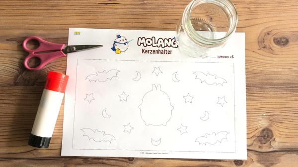 Eine Bastelvorlage, Schere, Kleber und ein Glas auf einem Holztisch | Rechte: KiKA