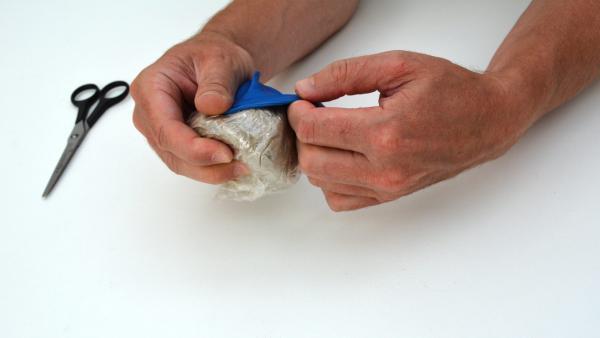 Stülpe den runden Teil eines Luftballons über die Tüte mit Sand.  | Rechte: KiKA