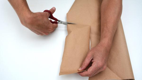 Um die Rollen miteinander zu verbinden, malst du zwei Rechtecke auf das Packpapier auf (ca. 7cm x 15cm) und schneidest diese mit der Schere aus.  | Rechte: KiKA