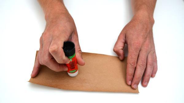 Jetzt trägst du auf eine Seite des Packpapiers Kleber auf. | Rechte: KiKA