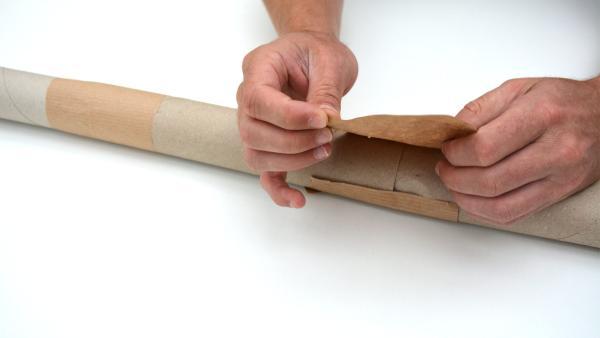 Dann kannst du die Verbindungsstücke mit dem Packpapier umwickeln. So halten die einzelnen Rollen fest zusammen.  | Rechte: KiKA