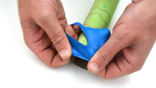 Den Hals des Luftballons stülpst du nun über ein Ende des Didgeridoos. So wird er zum Mundstück des Instruments. | Rechte: KiKA