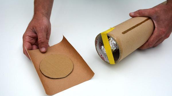 Streiche den Rand des Pappkreises und das restliche Packpapier mit etwas Kleber ein und setze den Pappkreis auf die Öffnung. Dabei ist es wichtig, erstmal nur eine Öffnung zu verschließen. Das andere Ende der Versanrolle bleibt noch offen.  | Rechte: KiKA