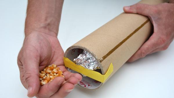 In die andere Öffnung füllst du nun den getrockneten Mais oder den Reis. | Rechte: KiKA
