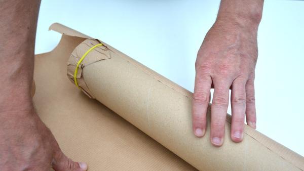 Umwickle die Versandrolle mit dem Packpapier. So kannst du ausmessen, wieviel Packpapier du benötigst, um die Rolle komplett zu umwickeln. Schneide das Packpier dann mit einer Schere entsprechend zu. | Rechte: KiKA