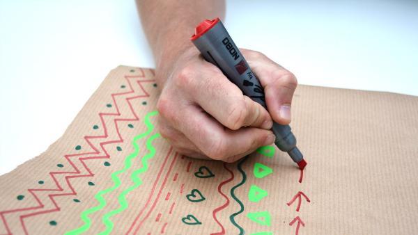 Bemale das zugeschnittene Packpapier nach deinen Wünschen. Hier gibt es kein Richtig oder Falsch. Durch die Bemalung wird jeder Regenmacher zum Einzelstück! | Rechte: KiKA