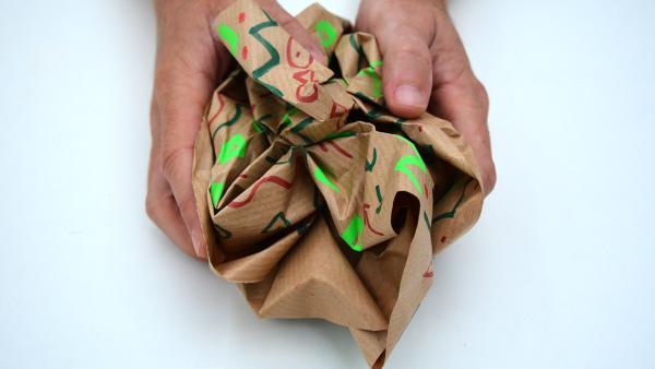 Jetzt nimmst du das bemalte Packpapier und drückst es mehrmals vorsichtig zusammen und wieder auseinander. Dadurch sieht die Oberfläche rauh und benutzt aus. | Rechte: KiKA
