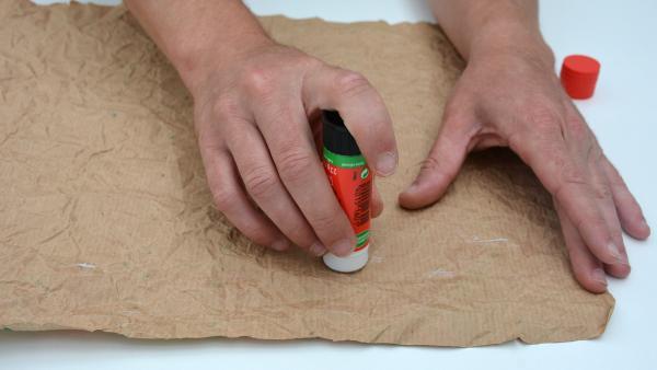Danach streichst du es wieder glatt und trägst auf die unbemalte Seite großzügig Kleber auf.  | Rechte: KiKA