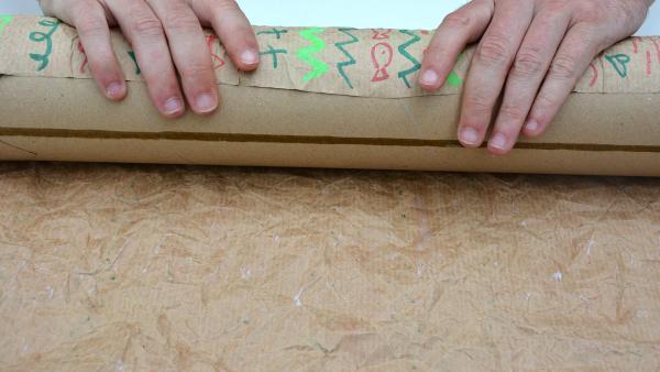 Jetzt umwickelst du die Versandrolle mit dem Packpapier. | Rechte: KiKA