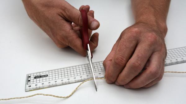 Schneide zwei Stücke des Bindegarn ab. Jedes Stück sollte dabei etwa 70 Zentimeter lang sein.   | Rechte: KiKA