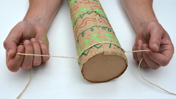 Schnüre die Bindegarn-Stücke um die Enden der Versandrolle und mache dann einen Knoten. Achte darauf, die Enden möglichst lang zu lassen. | Rechte: KiKA