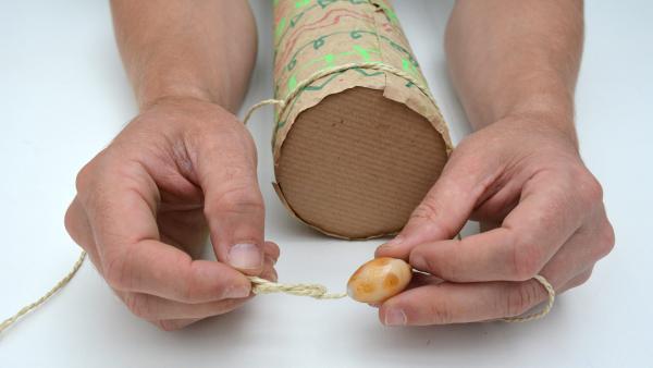 Fädele eine Perle auf jedes der vier Enden der Bindegarn-Stücke.  | Rechte: KiKA