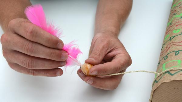Jetzt werden die Plastikfedern in die Öffnung der Glasperlen gesteckt. Durch den aufgetragenen Kleber sind sie fest und können nicht verrutschen.  | Rechte: KiKA