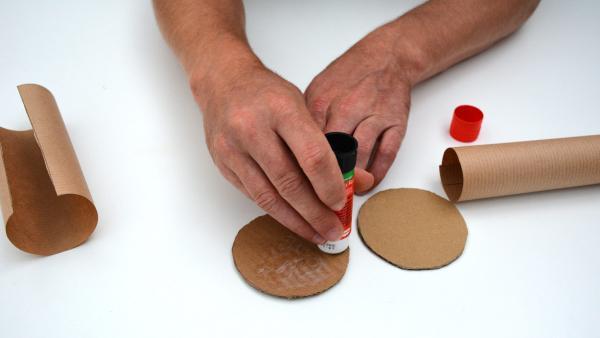 Trage dann etwas Kleber auf jeweils eine Seite der Pappkreise auf. | Rechte: KiKA