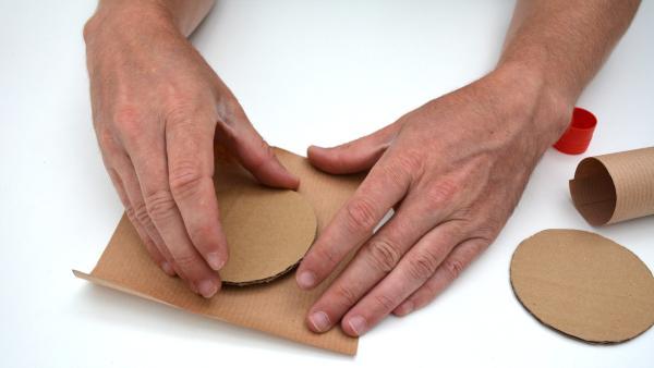 Klebe die beiden Pappkreise auf beiden Bögen Packpapier (15cm x 15cm). Achte darauf, sie möglichst mittig aufzukleben. | Rechte: KiKA