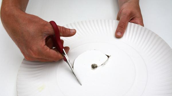 Stich mit der Schere in die Mitte des Papptellers. Schneide dann kreisförmig bis zum Rand ein großes rundes Loch in den Teller. | Rechte: KiKA