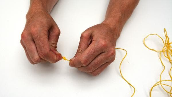 Nun schneidest du ein längeres Stück Garn ab. Die Länge kann zwischen 2 und 3 Metern betragen. An ein Ende des Garn machst du einen Doppelknoten. | Rechte: KiKA