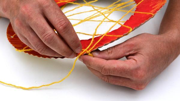Ziehe das Garn kreuz und quer durch alle Löcher - bis auf die drei Löcher, die zuerst ausgestanzt wurden. Damit erstellst du eine Art Spinnennetz. | Rechte: KiKA