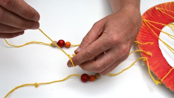Am unteren Ende machst du wieder einen Knoten in den Garn. So verhinderst du, dass die Kugeln vom Garn abrutschen können.  | Rechte: KiKA