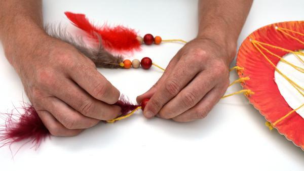 Trage nun etwas Flüssigkleber auf den unteren Teil der Federn auf und stecke sie in die unteren Löcher der Kugeln. Ziehe die Kugeln und die Feder nach unten bis zum Knoten.  | Rechte: KiKA