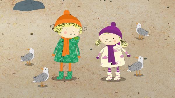 Eine Gruppe Möwen versammelt sich neben Nele und Nora am Strand. | Rechte: KiKA/Geronimo Productions
