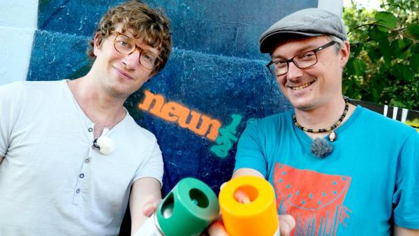 Robert und Sprayer Martin Scholz stehen mit Spraydosen in den Händen vor einer Graffiti-Wand, auf die das neuneinhalb-Logo gesprüht wurde. | Rechte: WDR/tvision