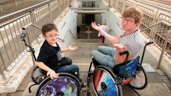Robert und Timon (li.) stehen vor den Treppenstufen am Troisdorfer Bahnhof. Beide sitzen im Rollstuhl. Timon seit er drei Jahre alt ist, Robert nur heute. | Rechte: WDR/tvision