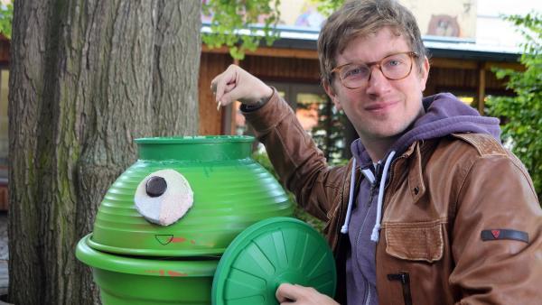 Robert wirft ein Kaugummi in einen lustigen, grünen Mülleimer mit einem Auge. | Rechte: WDR/tvision