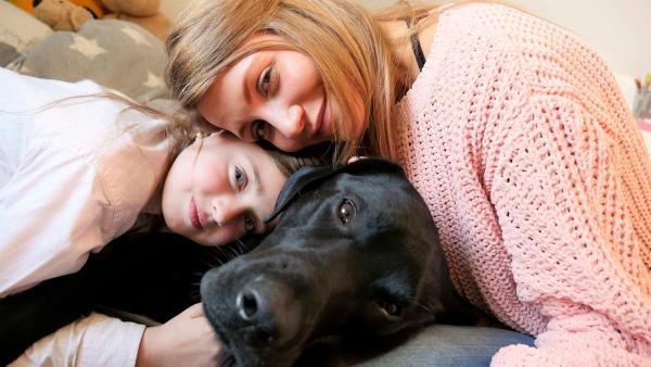 Jana und Siona kuscheln mit Sionas schwarzem Labrador Pluto. | Rechte: WDR/tvision
