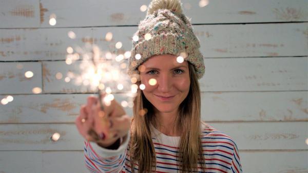 Jana hält eine funkensprühende Wunderkerze in der Hand. | Rechte: WDR/tvision