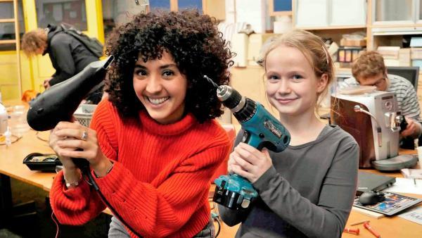 Siham (li) und Ella im Repair Café. Die beiden halten einen reparierten Fön und ihr Werkzeug, eine Bohrmaschine, in die Kamera. | Rechte: WDR/tvision