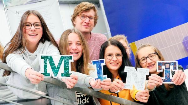 Robert zusammen mit einigen Schülerinnen im Schüler-Forschungslabor des Deutschen Zentrum für Luft- und Raumfahrt. Die Mädels halten die Buchstaben M – I – N – T in die Kamera. | Rechte: WDR/tvision