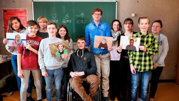 Robert mit einer Schulklasse im Klassenzimmer. Die Schüler und Schülerinnen halten Fotos von vier unterschiedlich aussehenden Kindern in den Händen. | Rechte: WDR/tvision