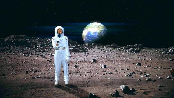 Mona steht in einem Raumanzug in einer Mondlandschaft. Im Hintergrund ist die Erde zu sehen. | Rechte: WDR/tvision