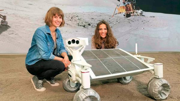 Mona (re.) und die Wissenschaftlerin Nadine sitzen neben einem Rover, der eines Tages auf dem Mond umherfahren soll. | Rechte: WDR/tvision