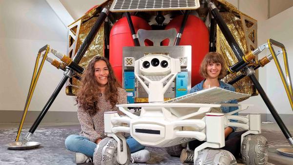 Mona (li.) und die Wissenschaftlerin Nadine sitzen vor einer Raumsonde, neben ihnen steht ein Rover, der eines Tages auf dem Mond umherfahren soll. | Rechte: WDR/tvision