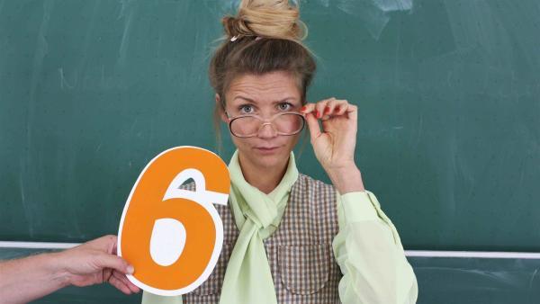 Jana steht als Lehrerin verkleidet vor einer Schultafel und blickt streng über ihre Brille hinweg. Sie möchte wissen, wie guter Unterricht geht und besucht dazu die Robert-Bosch-Gesamtschule in Hildesheim.  | Rechte: WDR/tvision
