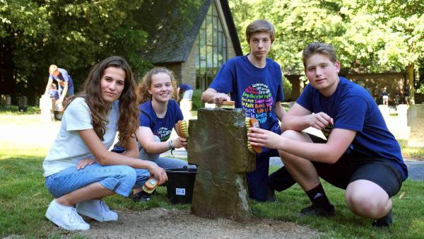 Mona (l) reinigt zusammen mit drei Jugendlichen ein Kreuz im Rahmen eines Workshops des Volksbunds. | Rechte: WDR/tvision