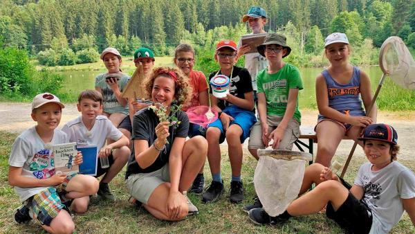 Gesa (3.v.l.) sitzt gemeinsam mit einer Gruppe junger Naturforscher*innen vor einem See. | Rechte: WDR/tvision