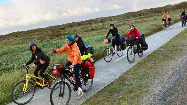 Die vier Jugendlichen treten auf den letzten Metern zu ihrem Ziel, dem Strand auf Texel, kräftig in die Pedale (v.l.n.r.): neuneinhalb-Reporterin Mona, Felix, Titus, Maren, Giulia, Jonas und Lara. | Rechte: WDR/tvision