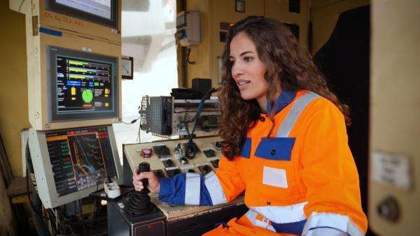 Reporterin Mona möchte herausfinden, warum es so viel Streit um den Braunkohleausstieg gibt. Dafür geht es in den Tagebau Garzweiler, wo sie einen riesen Schaufelradbagger steuern darf. | Rechte: WDR/tvision