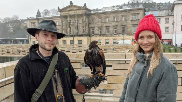 Reporterin Jana mit Falkner Ramon und dem Wüstenbussard Sieva am Wuppertaler Hauptbahnhof | Rechte: WDR/tvision
