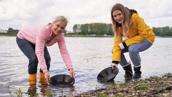 Um im Rhein Goldflitter finden zu können, braucht man einiges an Ausrüstung - zum Beispiel Goldwaschpfannen. Jana (r.) und die Goldschmiedin Silke im Flussbett. | Rechte: WDR/tvision